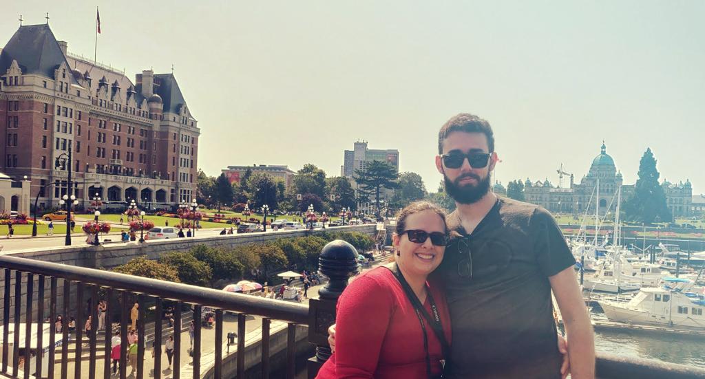 Eu e meu marido abraçados e ao fundo o The Empress Hotel e o Parlamento Britânico.